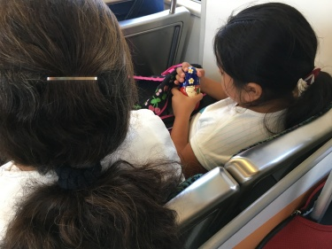 Little girls with nesting dolls on train